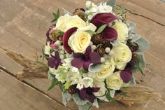 Bridal bouquet with purple calla lilies, purple dendrobium,stocks, scabiosa pods, ivory roses, brunias, pine corns and dusty miller. Designed by Forget-Me-Not Flowrs in Banff.