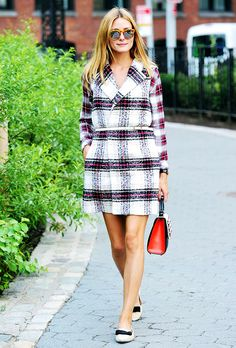 Olivia Palermo wears a long plaid vest over a plaid button-down shirt, paired with a white skinny belt around the waist, white flats, sunglasses, and a red and black handbag.