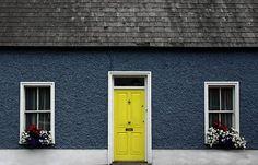dark blue stucco, bright yellow door