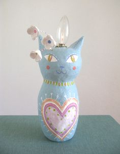 This blue cat was built over a battery operated plastic candelabra.  The light turns on and off by turning the bulb.