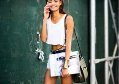 cutoff denim and a white crop top with a large gold bangle bracelet