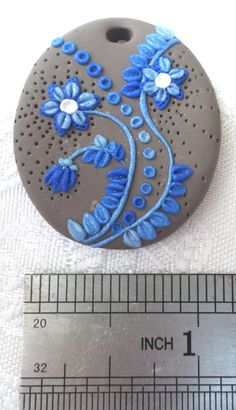Oval shaped polymer clay pendant, handmade with applique technique, one of a kind. Light brown, with flowers, stems, leaves and dots in blue to light blue gradient, decorated with puncture marks. By Lis Shteindel
