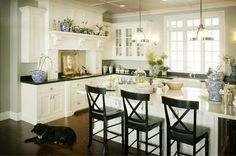 White cabinets, marble island, honed black granite, wood floor, grey walls, blue accents and black lab....PERFECT!