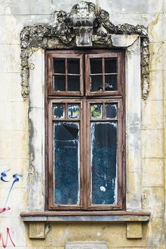 Old window with decorations, eroded by time