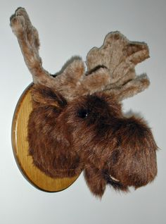 "Plush Moose Head ""Mitch"" Large Plaque Mount. Not too big and not too small. Mitch has deep fuzzy nostrils and a lower jaw. His nose is a little broader, and the bridge between his eyes is just the right size for wearing sunglasses. His antlers are plush fur fabric. PRODUCT SPECS: Ready to hang. Mitch's depth is 15"" from nose to wall. Adjustable antler span is 18"". Girth at shoulder is 25"". Plaque size is 9"" x 12""."