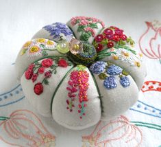 Embroidered Flowers on Linen pincushion.  Jill has a tutorial on how to make a basic pincushion, or you can order the finished item from her Etsy shop (link on this page).  Tutorial is here: http://fiberluscious.blogspot.com/p/classic-pincushion.html