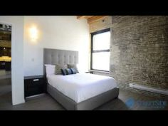 The KING at District Condos - Loft style conversion condos featuring exposed brick, century old wood beams, 14 ft ceilings and modern finishes. Gorgeous brick wall in master bedroom with grey upholstered bed frame