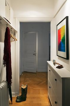 Personal and cozy apartment in Sweden | NordicDesign. Brilliant way to hang coats in an entry, using hooks to hold hangers.
