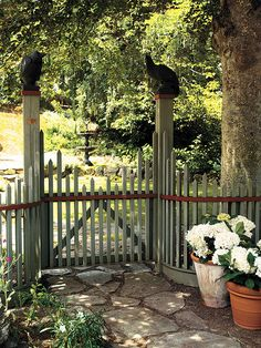 Victorian elegance..the graceful inward curve of the fence makes this gate a focal point and—along with the trim and colour scheme of the square pickets—captures the look of Victorian garden architecture. Carved crow-shaped finials add a gothic touch and playfully hint at the abundance of these feathered friends in the neighbourhood.