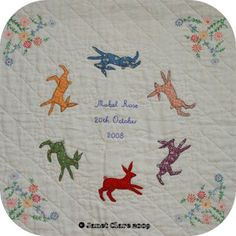 Janet Clare used a vintage embroidered tablecloth as the base and added her appliqued rabbits when designing this baby quilt.