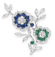 DIAMOND, SAPPHIRE AND EMERALD BROOCH. Van Cleef & Arpels. Designed as two intertwined circular-cut diamond flowers, with circular-cut and oval-cut sapphire and emerald petals, to the baguette-cut diamond stems, mounted in platinum Signed Van Cleef & Arpels (partially indistinct), N.Y., no. 30485