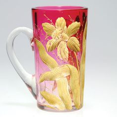 Humler & Nolan Rubina crystal handled mug, attributed to Moser. Twin Daffodils and foliage are intaglio carved about the surface and brought to life with bright gold. Numeral untis of measure are engraved alongside  the handle. Height 5 inches