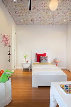 Bedroom: Fondness And Whimsy In A Minimalist Kids Bedroom. minimalist bedroom. patterned ceiling. floating balloon lighting. white bedding. red tufted cushions. white painted nightstand. red round table. wood flooring.