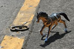 The Horse Project.  A invitational art project to tether tiny toy horses to the old-fashioned horse rings around Portland, Oregon.