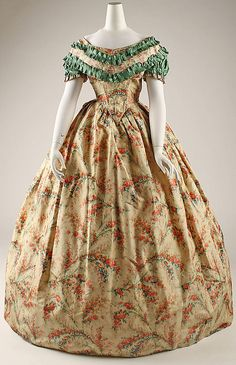 Printed silk, American, 1860-63. Low bodice, back opening, deep point, short sleeves, skirt with pleats. Silk box-pleated ruching. MET