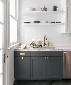 Natural light flows in front a window in this gorgeous white and gray contemporary kitchen featuring stacked white floating shelves mounted to all white subway tiles above a honed gray and white marble countertop accenting dark gray shaker cabinets and fitted with a marble sink and an aged brass gooseneck faucet.