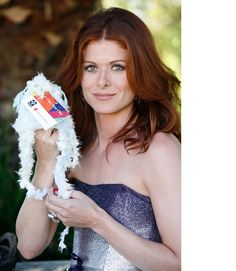 Debra Messing showing the baby cap she knit for charity, 2008 (a Sherpa-style cap in shades of pastel blue and yellow, with ear flaps to keep the baby's ears warm)