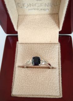Elegant three stone ring set with a centre cushion cut sapphire and two pear shaped diamonds on either side