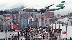 Hundreds of Hong Kong people gather onto Kai Tak Airport's rooftop parking garage to capture a momento of planes making their approach toward the runway.