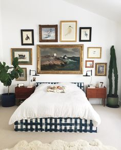 gallery wall in the bedroom / buffalo check bed / giant cactus / sheepskin rug