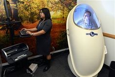 Kathleen Kossler, Schriever health promotion coordinator, inputs commands into a Bod Pod here Dec. 8,2014 Senior Airman Tympany Loggins, 21st Medical Squadron, helps Kossler test the machine. The Bod Pod measures body fat percentage. (U.S. Air Force photo/Christopher DeWitt)