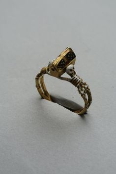 Jewelry   Jewellery   ジュエリー   Bijoux   Gioielli   Joyas   Art   Arte   Création Artistique   Artisan   Precious Metals   Jewels   Settings   Textures   Mourning-ring; enameled gold, the hoop enameled white, in the form of two skeletons supporting a coffin-shaped bezel with movable lid.