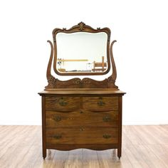 This vanity dresser is featured in a solid wood with a glossy oak finish. This small dresser has 4 serpentine front drawers, carved floral leaf accents and a curved swivel top mirror. Great for decorating a bedroom! #countryfarmhouse #dressers #vanitydresser #sandiegovintage #vintagefurniture