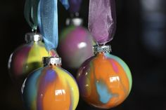 4 pour painted ornaments hanging from organza ribbons