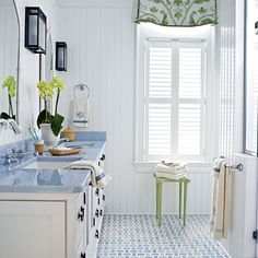 This master bath features bright white beaded board and sea glass-hued tile.