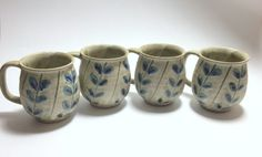 In their original box, a set of four Otagiri mugs, stoneware with blue leaves on a gray background. These pottery mugs are unique with their