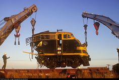 Two cranes pick up the remains of a Santa Fe F-unit at Hale Center, Texas by Joe McMillan