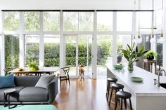 Floor to ceiling windows with a set of French doors let an impressive amount of light fall into the newly renovated open-plan living room and kitchen of this Federation style home in Melbourne. Photography: Martina Gemmola | Styling: Ruth Welsby