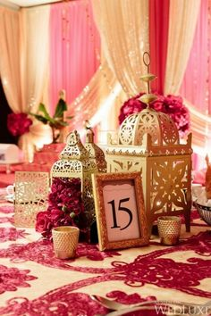 A rich Valentine's day themed Indian wedding reception complete with intricate gold lamps, gold framed table numbers, luscious pink and white lace inspired tableclothes and pink and white drapery. Indian Wedding Centerpieces, Wedding Lanterns, Indian Theme, Moroccan Theme, Moroccan Wedding Theme, Indian Reception, Indian Wedding Receptions, Reception Ideas, Bollywood Wedding