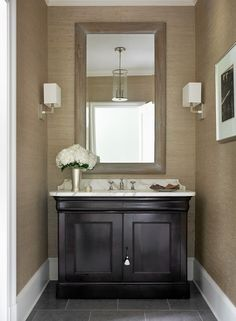 Powder room with wallpaper. The wallpaper in this powder room is the Philip Jeffries Metallic Paper Weaves in color Titanium. Interior Design by Beth Webb Interiors.