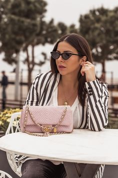 Stella Asteria wearing striped blazer with pink Chanel Chevron bag and cat-eye sunglasses