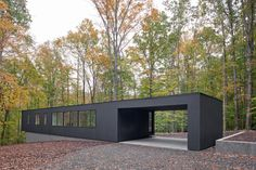 The Corbett Residence is on a wooded site, down a winding drive. The drive is thin and meanders between trees to protect the house from view. The house is a low black box that strikes a line across the slope, mimicking the horizon. The house is at the Container House Plans, Container House Design, Container Pool, Shelters In The Woods, Container Buildings, Shed Homes, Shipping Container Homes, Shipping Containers, Modern House Design