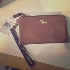 24% REDUCTION SALE NWT coach wristlet. NWT Coach wristlet great for a night on the town. Nice brown leather that virtually goes with everything. The wristlet has two compartments one fits your phone and the other your money and credit cards. It has been tested with the newest iPhone 6s and it is a match made in heaven. Coach Bags Clutches & Wristlets