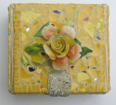 Bright and sunny pique assiette mosaic cigar box, an old rhinestone shoe ornament, and Capodimonte flower.  The yellow shards are from a broken McCoy fruit compote, the bottom part of it; this is one of my favorite shades of yellow.