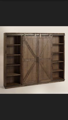 World Market Wood Farmhouse Barn Door Bookcase! A substantial storage solution with adjustable and removable shelving, our bookshelf is crafted of distressed solid wood with rustic metal accents that give it the look of an old barn door. Configure the sliding doors to organize and display books, photos and collectibles with a personalized touch.