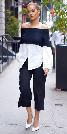 If Rita Ora had to work in an office, we'd guess this would be her take on workwear. She recently stepped out in a sweater-button-down hybrid off-shoulder top that she expertly styled with pleated cropped pants and white pumps.
