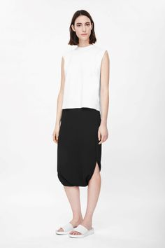 A modern design, this crepe pencil skirt has a closed hem and a split opening for each leg on the sides. Designed to sit just below the waist and fall on the calf, it has a darted waistline and hidden side-zip fastening.