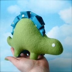 Handmade dinosaur baby toy. Made out of fern green fleece, with two rows of ruffles down the back.
