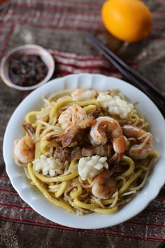 250 g thick round rice noodles 250 g thick round yellow noodle (Hokkien Noodle) 250 g prawns, shells on 200 g pork belly, thinly sliced 1 pc medium sized squid, sliced 8 pcs fish balls, sliced in half 2 cups chicken stock 2 eggs, lightly beaten 4 cloves garlic, minced 2 tsp sesame oil 2 tsp soy sauce fish sauce white ground pepper oil