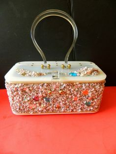 """Here is a wonderful survivor from the 1950's. This adorable purse is in such excellent condition and it is a stunning item.The base is lucite- the handle is clear and beautifully arched. The top and bottom is white lucite.The four sides of the purse is covered with small pink and white sea shells. The inside has the label-"""" Originals by Midas of MIami."""