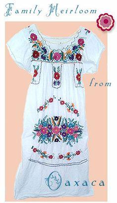 Bata blanca bordada en hilos de colores variados.