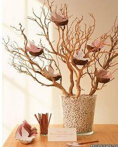 Un arbre a messages  Une arbre (recréé avec des branches) et piquées dans un pot en verre. Ensuite, des nids d'oiseaux sont disposés dans chaque branche et des faux oiseaux en papier. Cela peut etre un simple décor, ou bien etre très utile, comme ici: l'arbre sert de livre d'or: chaque invité écrit un mot sur les oiseaux en papier et laisse un message aux mariés en l accrochant a l'arbre
