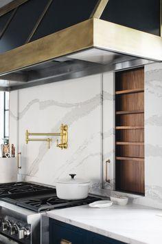 marble backsplash with brass and black hood