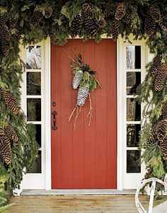Pine cone arrangement on door with thick swag of garland. (Photo: Country Living)
