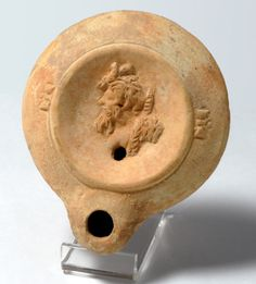 Roman 1st century lamp with satyr.  A Roman buff coloured oil lamp with discus moulded to show the profile head of a satyr with beard and moustache.    The Levant: Circa 1st century A.D.