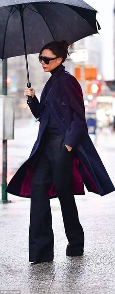 Walk this way: Despite the downpour, she looked incredibly chic in her high-waisted flares...